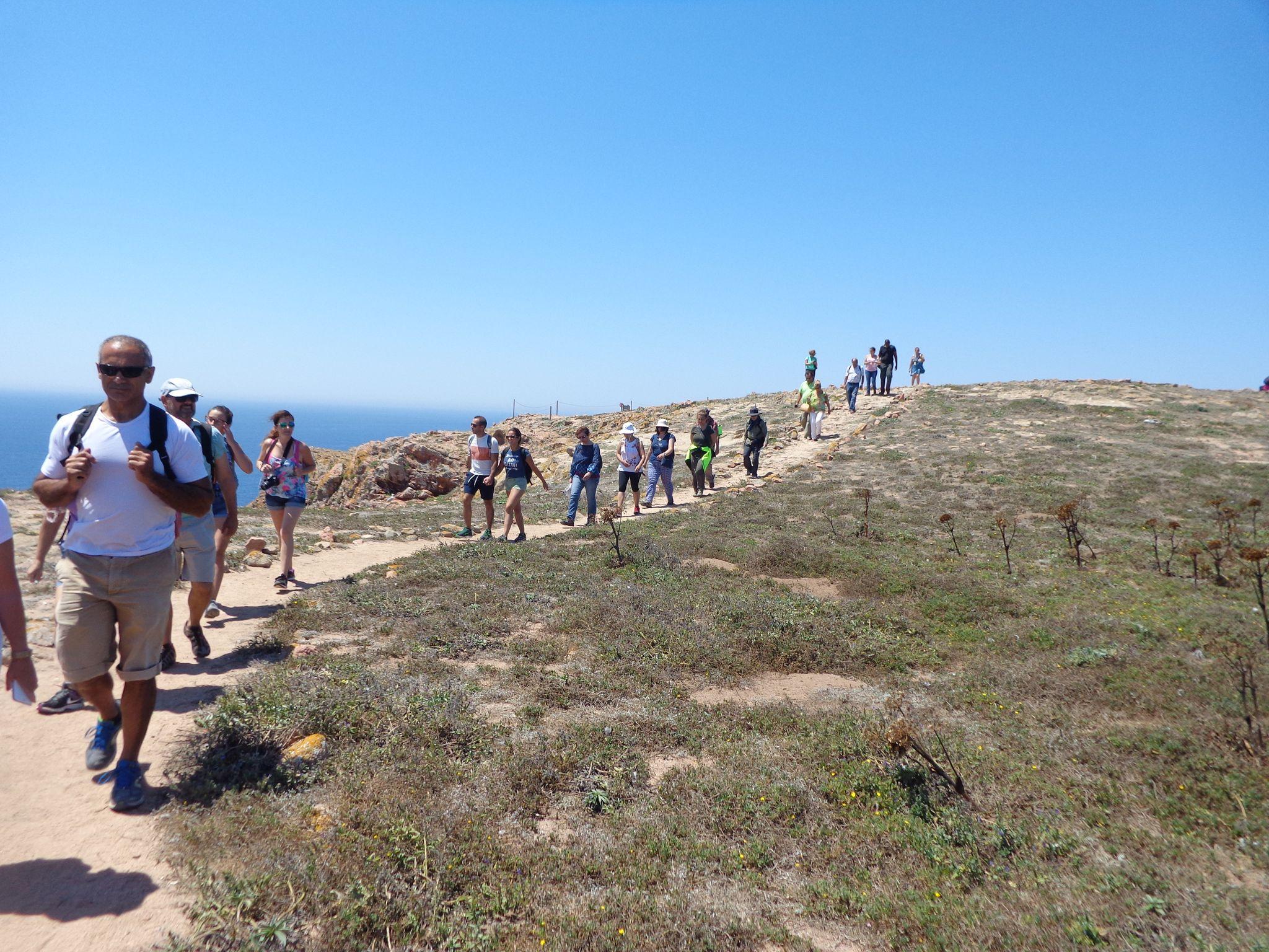 Grupo em caminhada na encosta de uma falésia junto ao mar